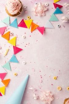 Bovenaanzicht van verjaardagsslinger en cupcakes