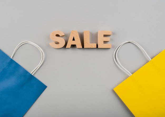 Bovenaanzicht van verkoop letters met gele en blauwe tas