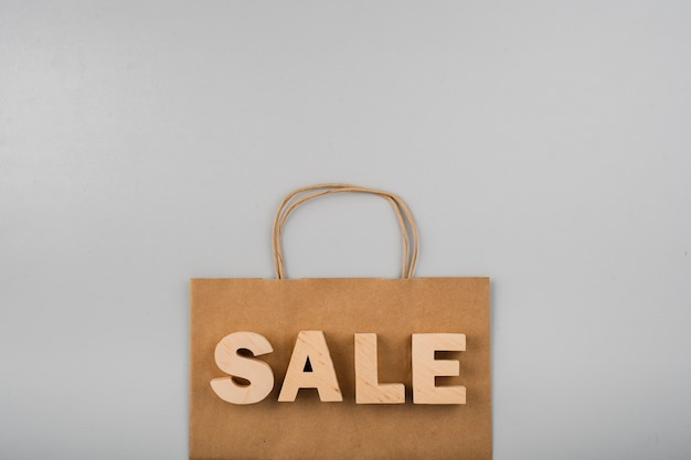 Bovenaanzicht van verkoop letters met papieren zak op effen achtergrond