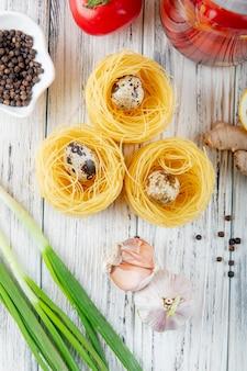 Bovenaanzicht van vermicelli met mini eieren zwarte peper korrels knoflook lente-ui op houten achtergrond