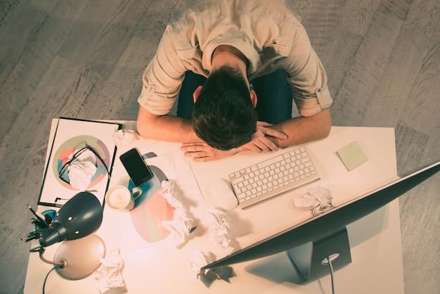 Bovenaanzicht van vermoeide man slapen op tafel in kantoor