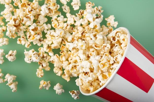 Bovenaanzicht van vernietigde gestreepte papieren beker met heerlijke verse popcorn