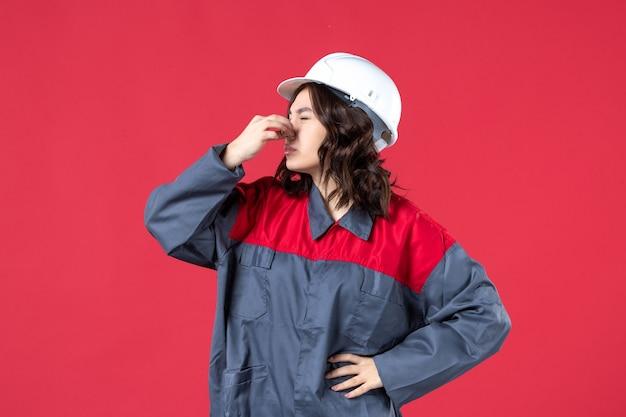 Bovenaanzicht van verontrustende vrouwelijke bouwer in uniform met harde hoed en houdt haar neus op geïsoleerde rode achtergrond