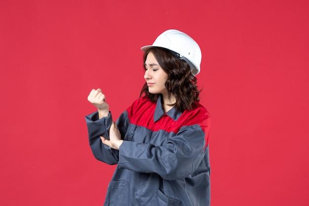 Bovenaanzicht van verontrustende vrouwelijke bouwer in uniform met harde hoed en lijden aan handpijn op geïsoleerde rode achtergrond