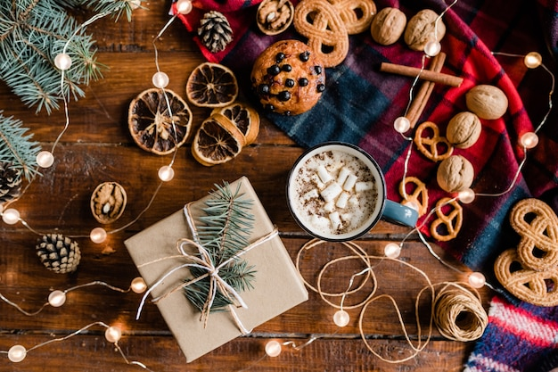 Bovenaanzicht van verpakt geschenk omgeven door warme drank, dennenappels, koekjes, walnoten, draden, naaldboom en slingers op houten tafel