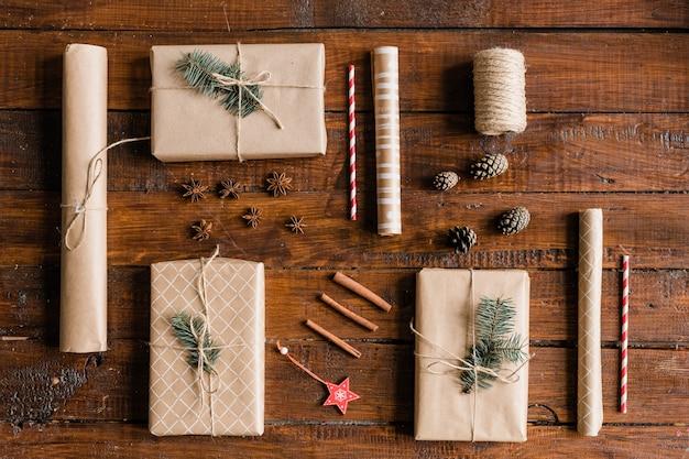 Bovenaanzicht van verpakte en verpakte geschenkdozen, opgerold papier, dennenappels, decoraties, draden, kaneel en steranijs op houten tafel