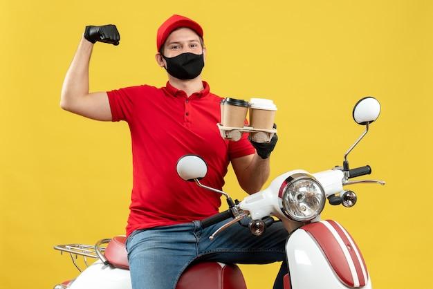 Bovenaanzicht van verrast bezorger dragen uniform en hoed handschoenen in medische masker zittend op scooter met bestellingen tonen zijn gespierde