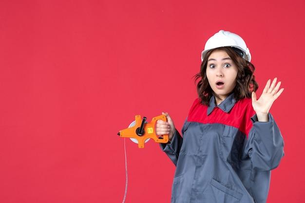 Bovenaanzicht van verrast emotionele vrouwelijke architect in uniform met harde hoed opening meetlint op geïsoleerde rode achtergrond
