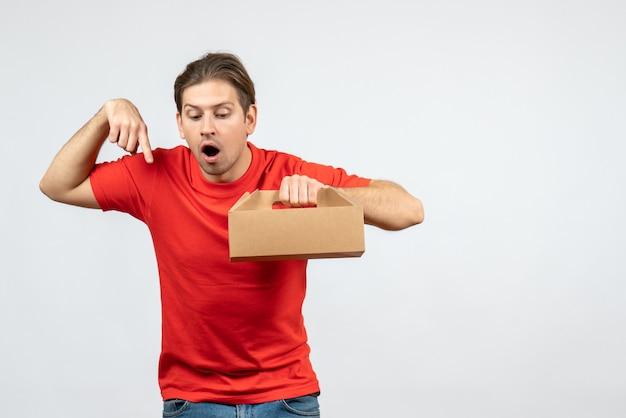 Bovenaanzicht van verrast jonge man in rode blouse bedrijf doos neerkijkt op witte muur