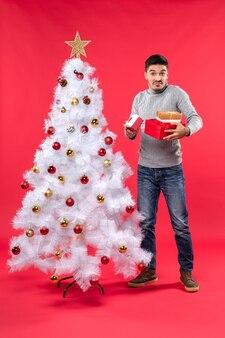 Bovenaanzicht van verrast knappe volwassene in een grijze blouse staande in de buurt van de versierde witte kerstboom