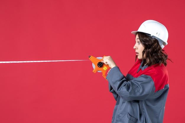 Bovenaanzicht van verrast vrouwelijke architect in uniform met harde hoed opening meetlint op geïsoleerde rode achtergrond