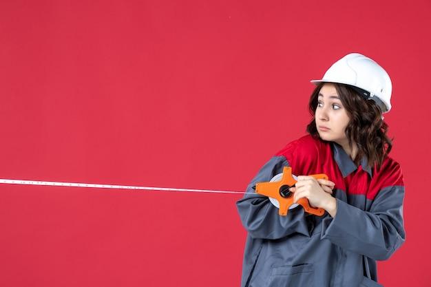 Bovenaanzicht van verraste vrouwelijke architect in uniform met veiligheidshelm die meetlint opent en terugkijkt op geïsoleerde rode achtergrond