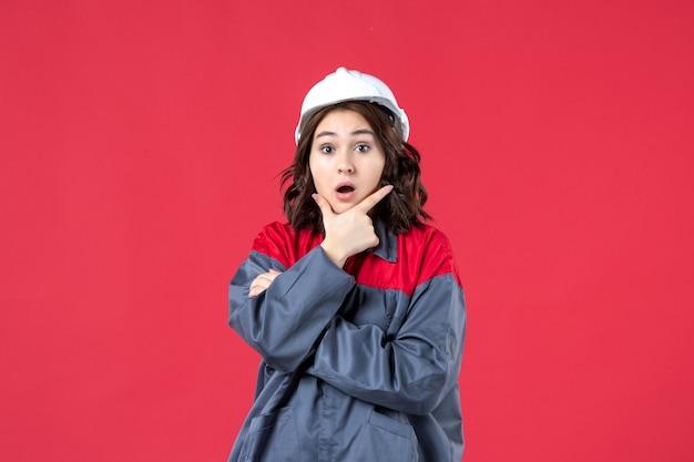 Bovenaanzicht van verraste vrouwelijke bouwer in uniform met helm en geconcentreerd op iets op geïsoleerde rode achtergrond