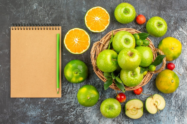 Bovenaanzicht van verre appels appels in de mand citrusvruchten kersen crème notebook potloden