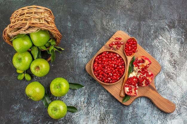 Bovenaanzicht van verre appels appels met bladeren in de mand granaatappel zaden op het bord