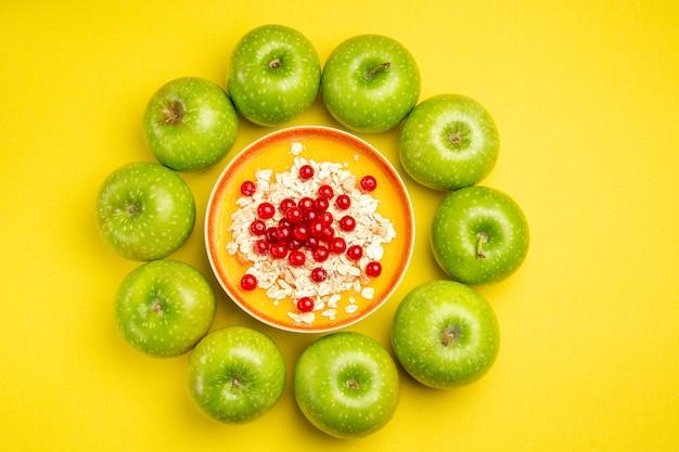Bovenaanzicht van verre appels groene appels kom rode aalbessen havermout op de gele tafel