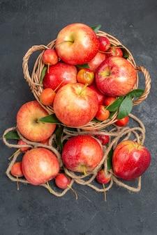 Bovenaanzicht van verre appels touw de smakelijke appels rood-gele kersen in de mand