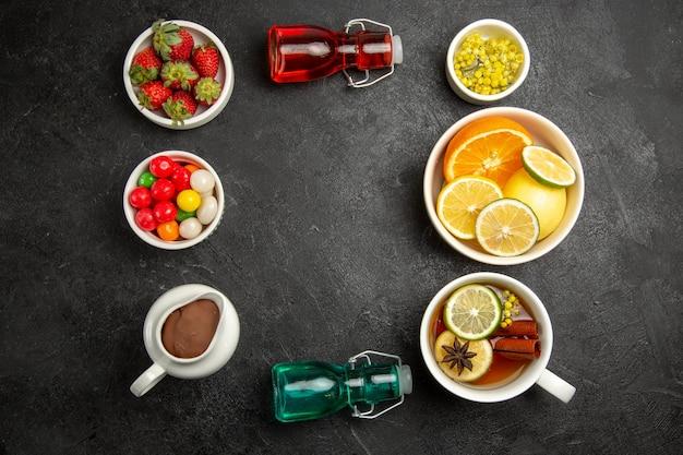Bovenaanzicht van verre bessen en chocoladekommen met chocoladeroomsnoepjes, kruiden, aardbeien en gesneden citroenen naast het kopje thee en kleurrijke flessen