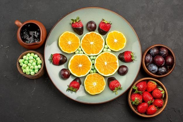 Bovenaanzicht van verre bessen en chocoladeplaat van gehakte sinaasappel en met chocolade bedekte aardbeien naast de kommen met snoepbessen en chocoladesaus