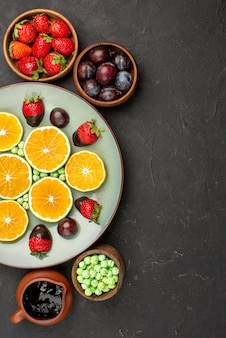 Bovenaanzicht van verre bessen en chocoladeplaat van gehakte sinaasappel en met chocolade omhulde aardbeien naast de kommen met bessensnoepjes en chocoladesaus