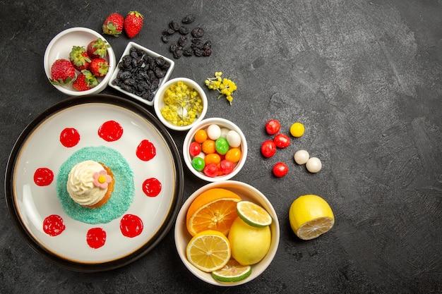 Bovenaanzicht van verre bessen en fruitcake met sauzen en room naast de witte kommen met aardbeien, limoenen, citroenen, sinaasappels en kleurrijke snoepjes op tafel