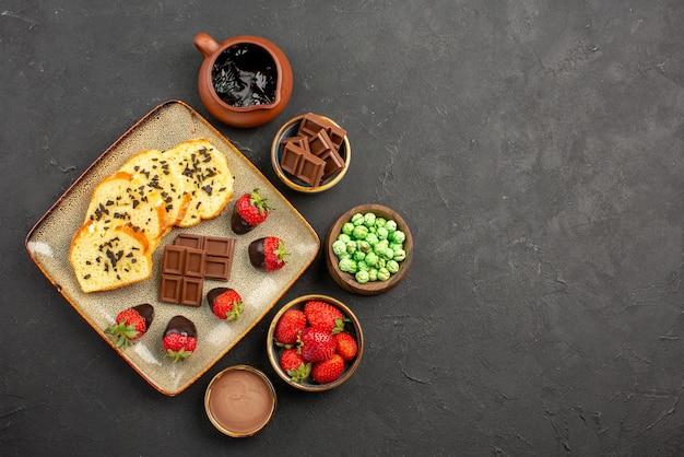 Bovenaanzicht van verre cake en aardbeien kommen met chocolade aardbeien, groene snoepjes en chocoladeroom naast het bord cake met met chocolade omhulde aardbeien