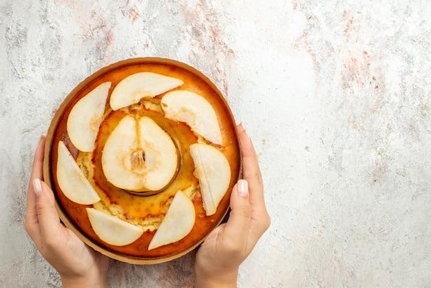 Bovenaanzicht van verre cake met peren smakelijke cake met peren in handen op de witte achtergrond