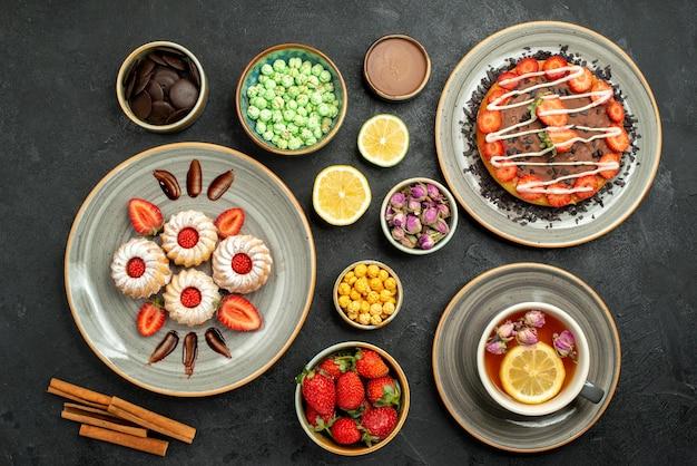 Bovenaanzicht van verre cake met snoep cake met chocolade en aardbei zwarte thee citroenen plaat van koekjes met aardbei kommen chocolade en verschillende snoepjes op zwarte tafel