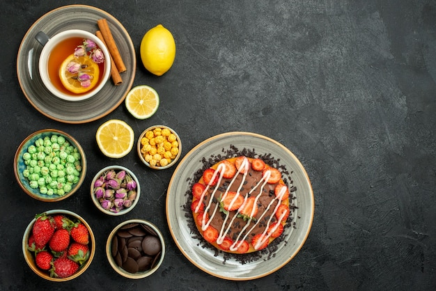 Bovenaanzicht van verre cake met snoepcake met aardbei en chocolade zwarte thee met citroen-hizelnoten kommen met chocolade en verschillende snoepjes aan de linkerkant van de donkere tafel
