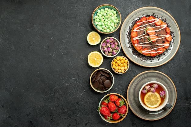 Bovenaanzicht van verre cake met thee smakelijke cake met chocolade en aardbei zwarte thee citroenen kommen met chocolade en verschillende snoepjes aan de rechterkant van zwarte tafel
