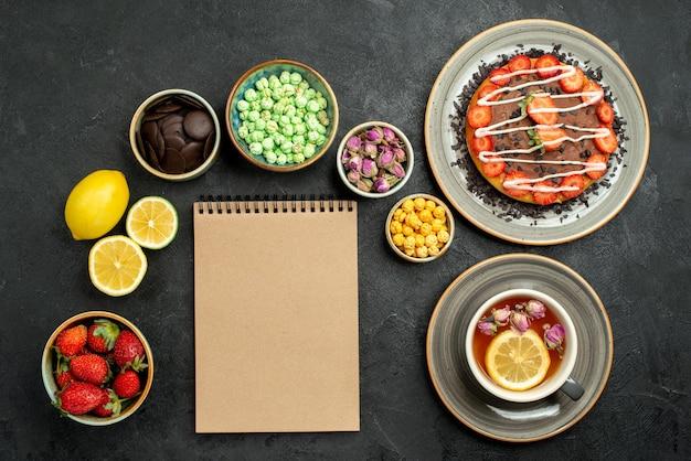 Bovenaanzicht van verre cake met thee smakelijke cake zwarte thee citroenen chocolade en verschillende snoepjes naast crème notebook op zwarte tafel