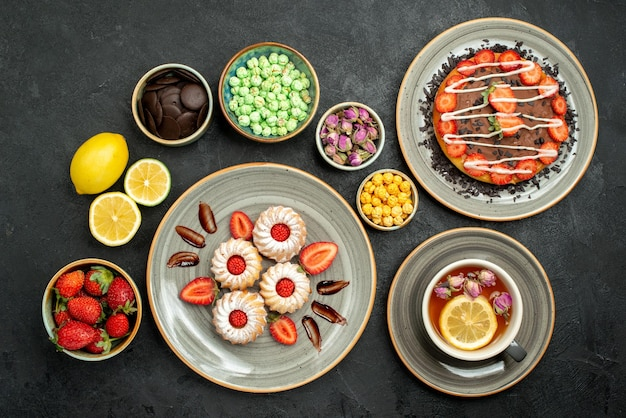 Bovenaanzicht van verre cake met thee smakelijke cake zwarte thee koekjes met aardbei in witte plaat naast citroenen chocolade en verschillende zoetigheden op zwarte tafel
