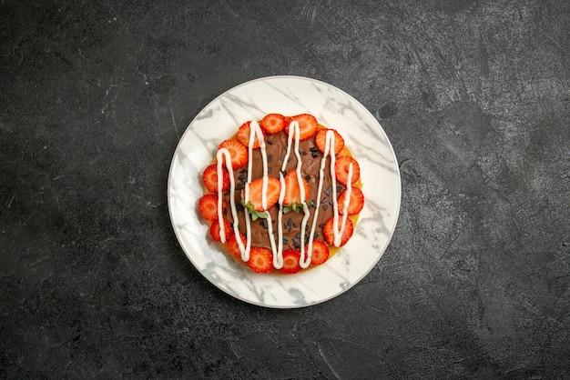 Bovenaanzicht van verre cake op bord smakelijke cake met chocolade en aardbeien op de witte plaat op het donkere oppervlak