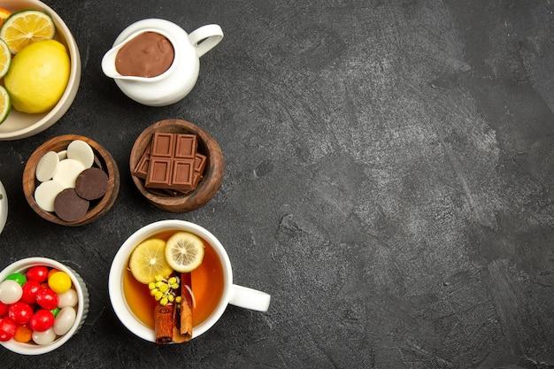 Bovenaanzicht van verre chocolade en citroenchocoladeroomsnoepjes en citroenen in kommen naast het kopje kruidenthee op de donkere tafel
