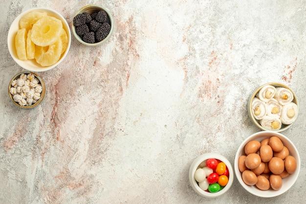 Bovenaanzicht van verre citroencake zes kommen snoep aan de rechter- en linkerkant van de witte achtergrond