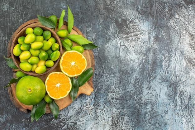Bovenaanzicht van verre citrusvruchten citrusvruchten in de kom sinaasappelen mandarijnen op het bord