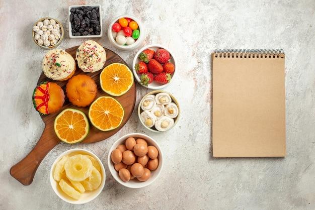 Bovenaanzicht van verre citrusvruchten op het bord gesneden sinaasappel en koekjes op de houten snijplank naast de crèmekleurige notitieboekjes met snoep en gedroogde ananas