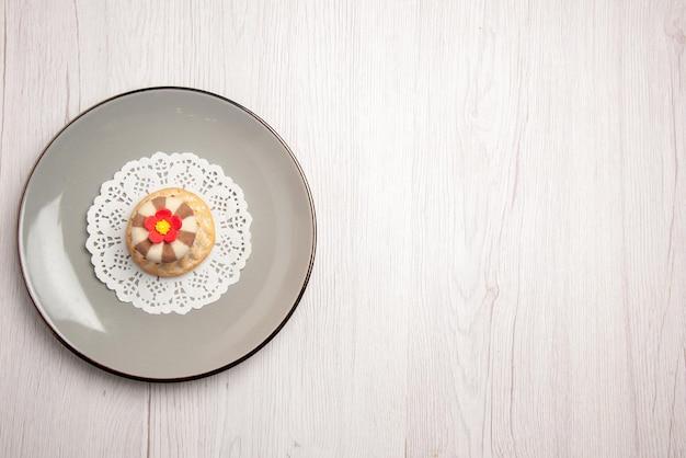 Bovenaanzicht van verre cupcake cupcake op het witte kanten kleedje aan de linkerkant van de tafel