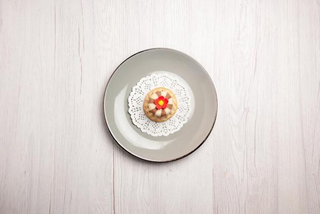 Bovenaanzicht van verre cupcake cupcake op het witte kanten kleedje op de grijze plaat op tafel