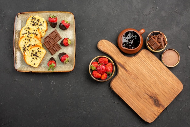 Bovenaanzicht van verre dessertcake met met chocolade omhulde aardbeien en chocolade en snijplank tussen kommen chocoladeroom en bessen op tafel