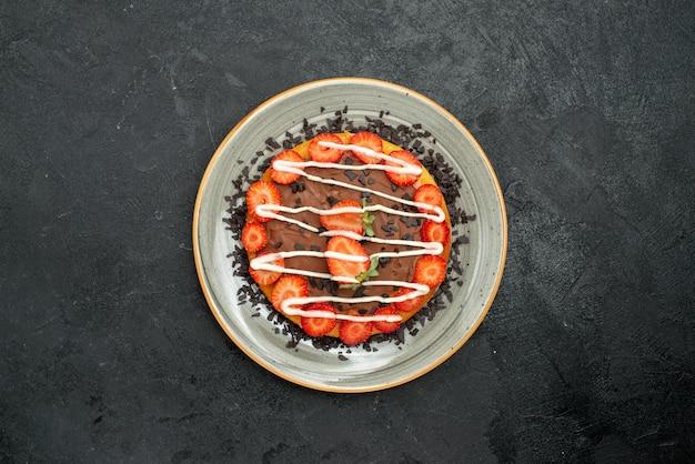 Bovenaanzicht van verre dessertcake met stukjes aardbei en chocolade op een witte plaat in het midden van een donkere tafel