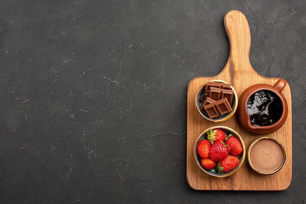 Bovenaanzicht van verre dessertkommen met smakelijke chocoladeroom en aardbeien op de snijplank aan de rechterkant van de donkere tafel