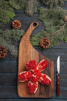 Bovenaanzicht van verre granaatappel aan boord van rode gepilde granaatappel op snijplank naast mes en sparren takken met kegels op tafel