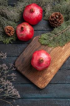 Bovenaanzicht van verre granaatappels en kegels smakelijke granaatappel op snijplank naast twee granaatappels en takken met kegels op grijs oppervlak