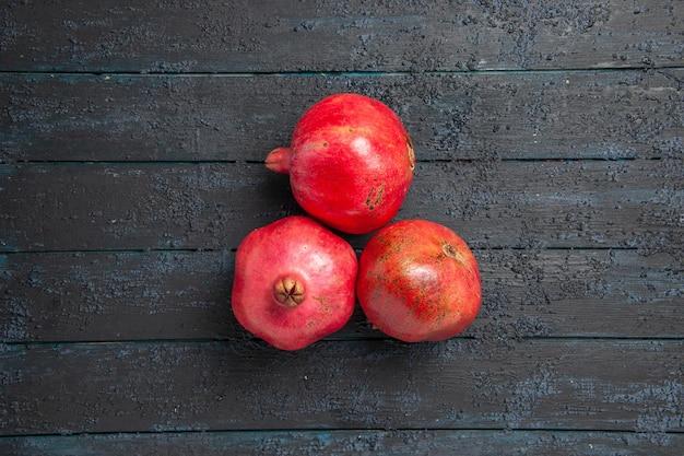 Bovenaanzicht van verre granaatappels op tafel drie rode granaatappels op donkere tafel