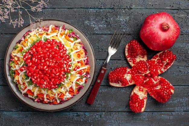 Bovenaanzicht van verre granaatappels op tafel gepelde granaatappel naast de vork en bord op de grijze tafel