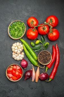 Bovenaanzicht van verre groenten tomaten met steeltjes hete pepers knoflook kruiden specerijen citrusvruchten