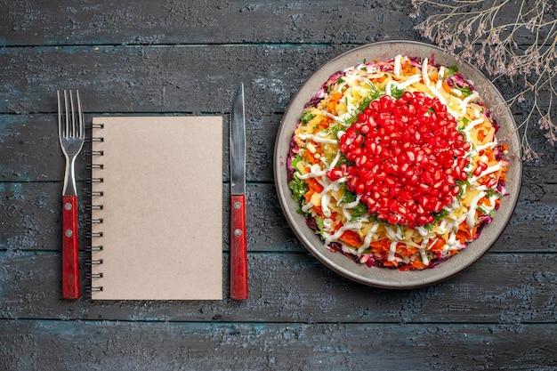 Bovenaanzicht van verre kerstschotel kerstschotel met granaatappelpitten naast het witte notitieboekje met vork en takken op de donkere tafel