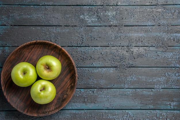 Bovenaanzicht van verre kom appels bruine kom smakelijke groene appels aan de linkerkant van donkere tafel