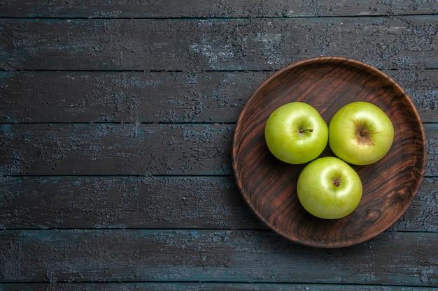 Bovenaanzicht van verre kom appels bruine kom smakelijke groene appels aan de rechterkant van donkere tafel